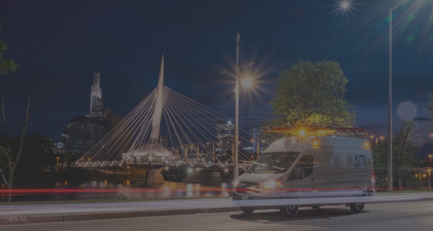 Background image of an ACME van driving past the Provencher Bridge in Winnipeg.