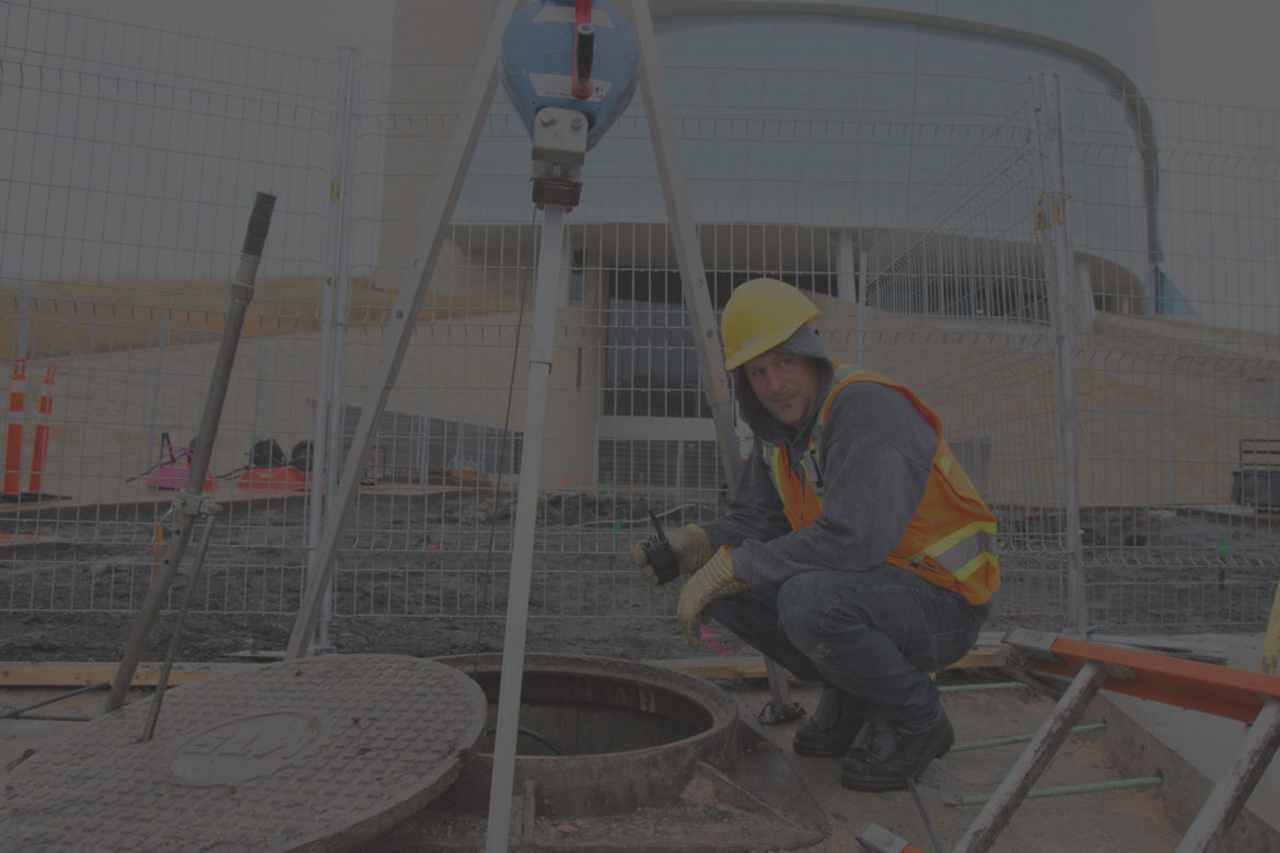 Background image of a man monitoring a coworker in a manhole.