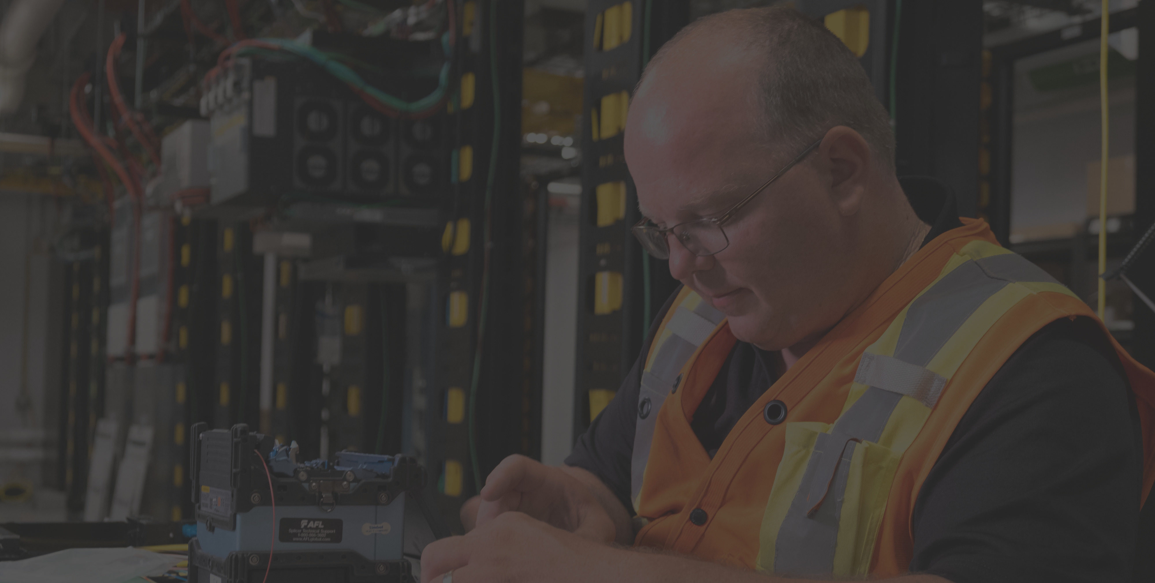 Background image of a man splicing fiber optic cabling.