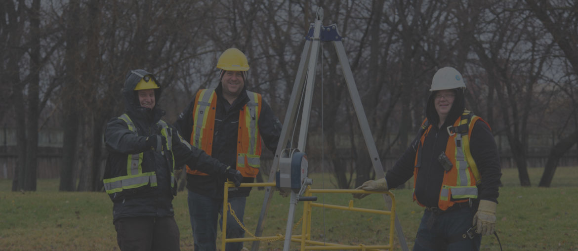 Background image of a men setting up manhole entry equipment.